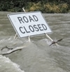 Road closed sign engulfed in water