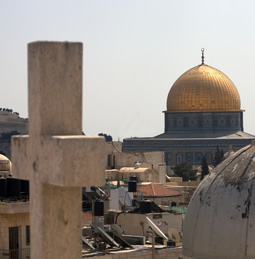 a cross in the foreground with a mosque in the background
