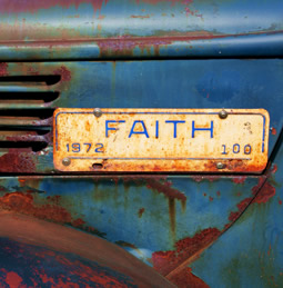 a sign saying \'Faith\' on an old truck