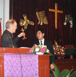 presenting a cross to a Chinese man