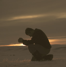 a man kneeling in prayer in the desert
