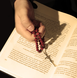 a hand on a bible holding a cross