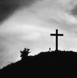 a cross on a hill with a figure standing in front