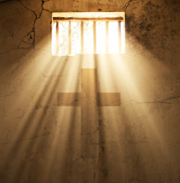 Light streaming through bars onto a cross