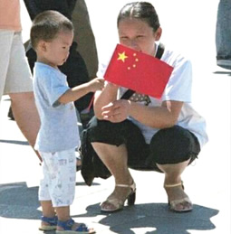 A Chinese lady and her son holding a flag