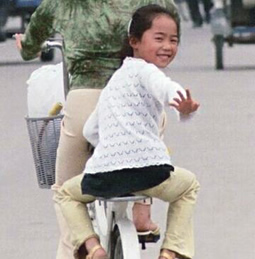Chinese girl on the back of a bicycle
